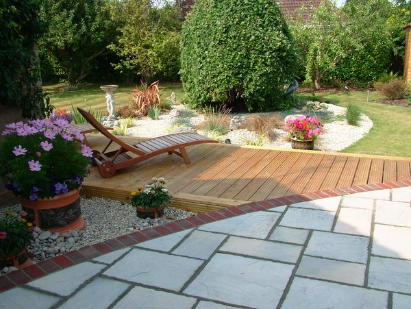 garden design Sandstone and decking curved brick edging