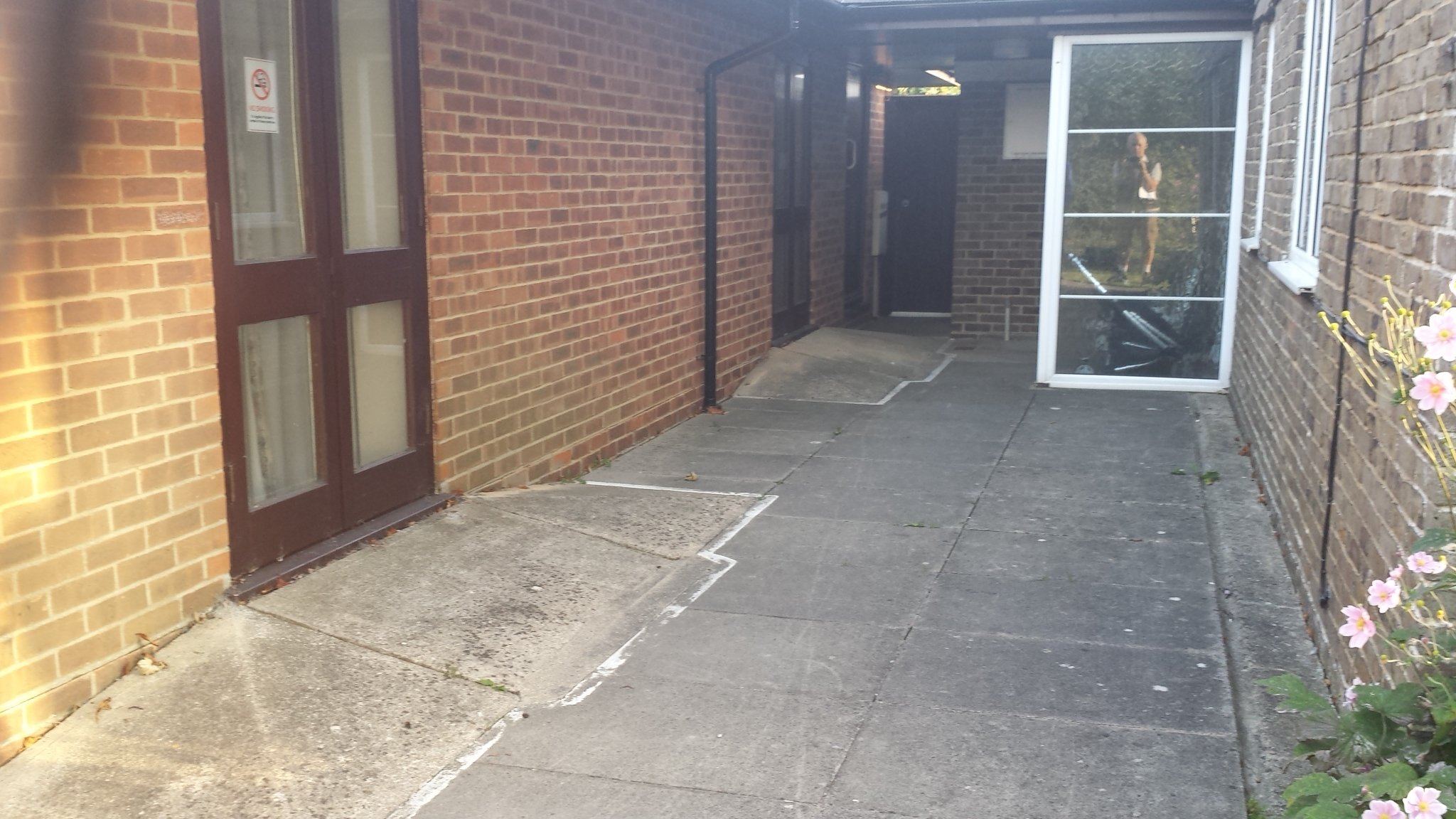 Removal concrete ramp near white frame glass partition and make good with granite grey resin bound aggregate